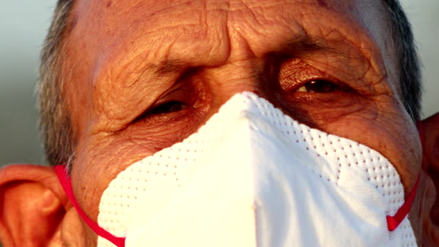 senior men covering his face with pollution mask for protection from viruses - india stock videos & royalty-free footage
