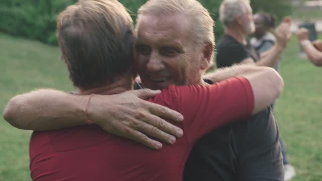 vidéos et rushes de senior men embracing after practicing boxing in park - musculation