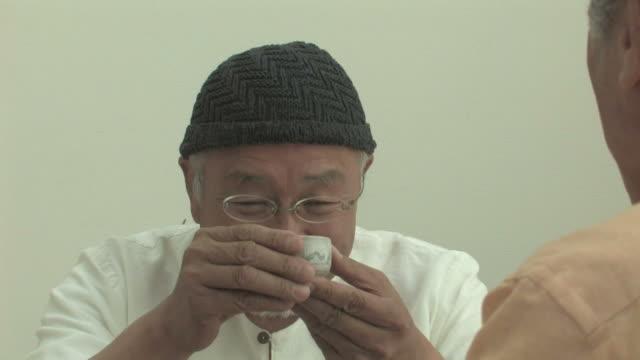 senior men enjoying sake - アクティブシニア点の映像素材/bロール