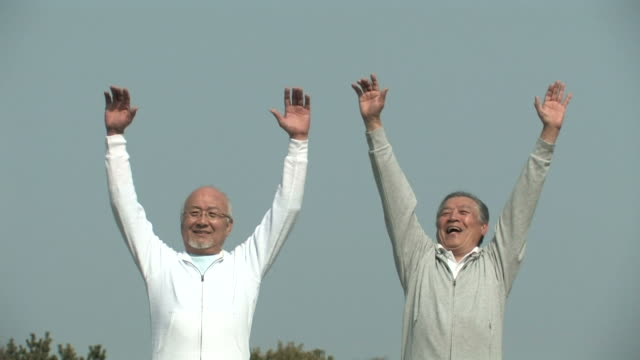 Senior men holding up arms