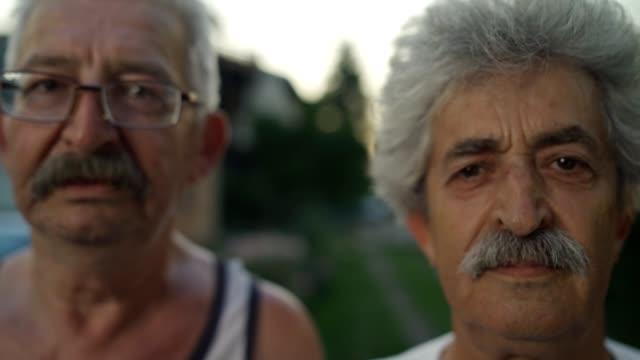 vidéos et rushes de hommes aînés regardant la caméra - visage sans expression