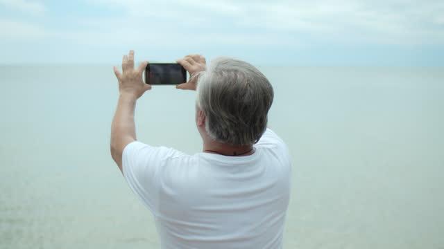 夏休みでシニア男性が写真を撮る - 受話器点の映像素材/bロール