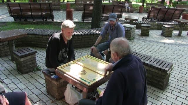 Senior men playing backgammon in Taras Shevchenko Park in Kiev capital of Ukraine