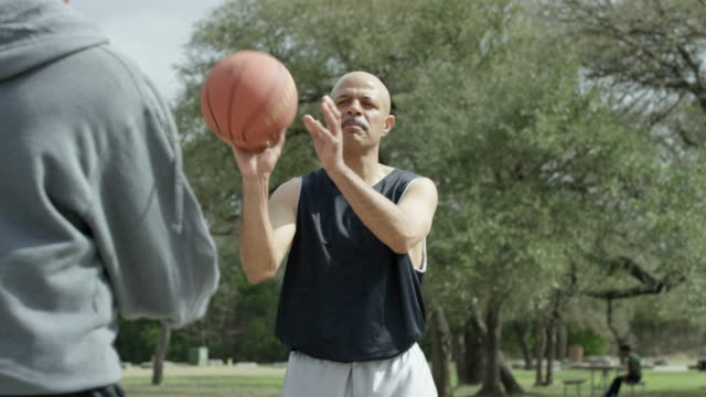 senior men playing basketball together in an urban park - mature men stock videos & royalty-free footage