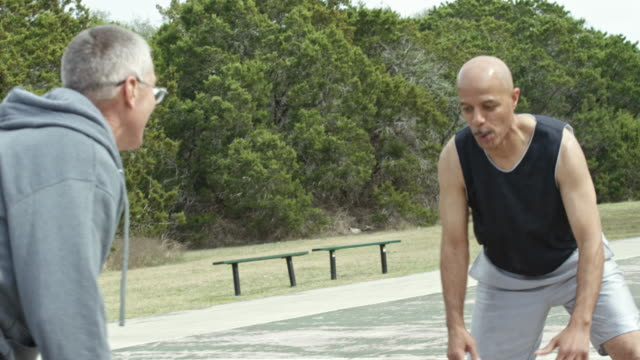 senior men playing basketball together in an urban park - 55 59 jahre stock-videos und b-roll-filmmaterial