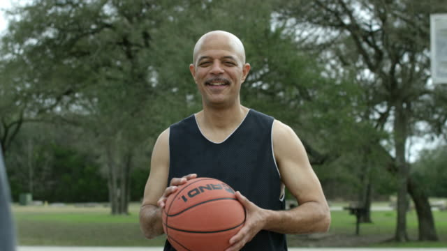 senior men playing basketball together in an urban park - shorts stock videos & royalty-free footage