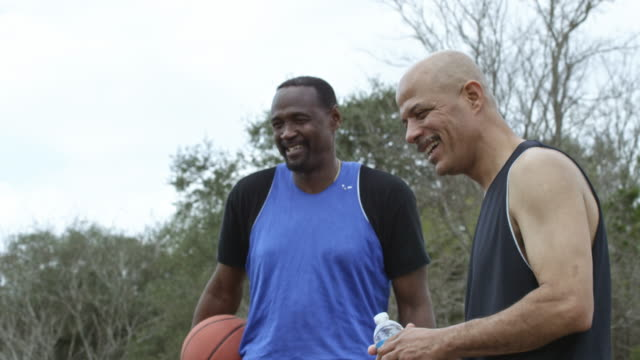 Senior men playing basketball together in an urban park