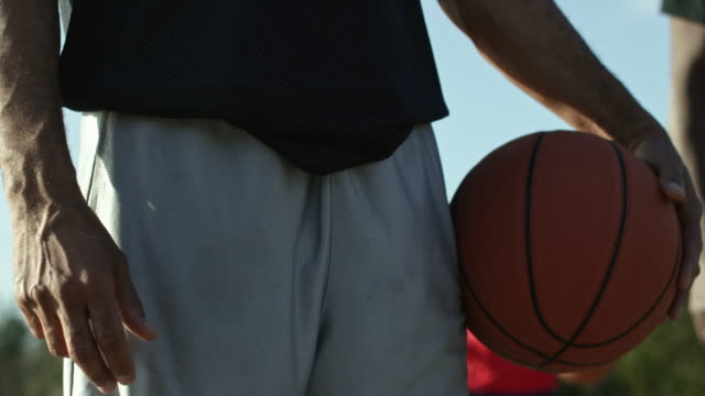 vidéos et rushes de senior men playing basketball together in an urban park - buste partie du corps