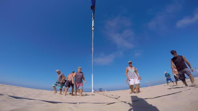 POV of senior men playing beach volleyball. - Slow Motion