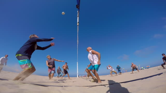 POV of senior men playing beach volleyball.
