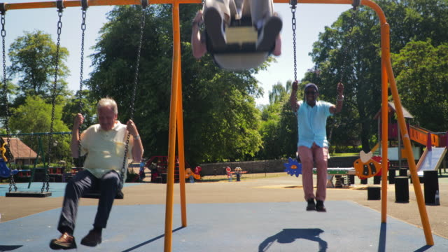senior men playing on the swings - swinging stock videos & royalty-free footage