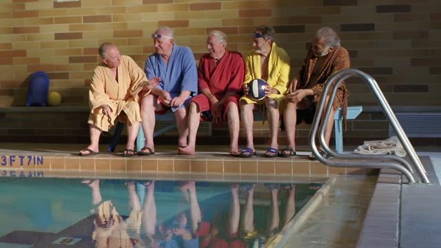 ws senior men sitting side by side on poolside bench / seattle, washington, usa - 水泳パンツ点の映像素材/bロール