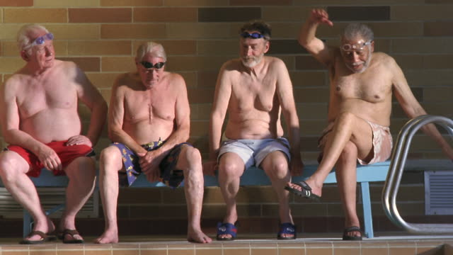 ws pan senior men sitting side by side on poolside bench / seattle, washington, usa - side by side stock videos & royalty-free footage