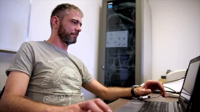 vídeos y material grabado en eventos de stock de desarrollador de software senior masculino en la oficina - software de ordenador