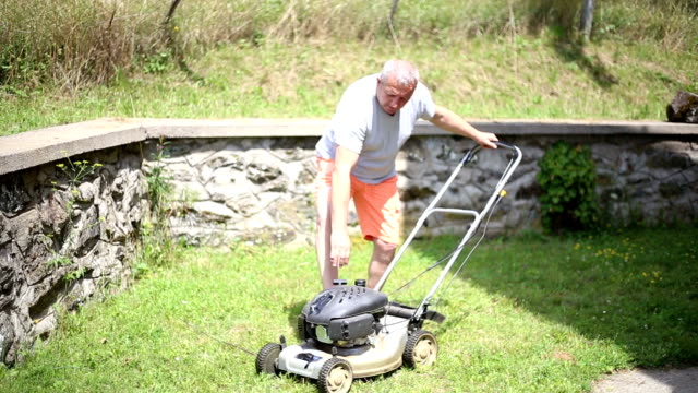 senior men starting electric lawnmowers - lawn mower stock videos and b-roll footage