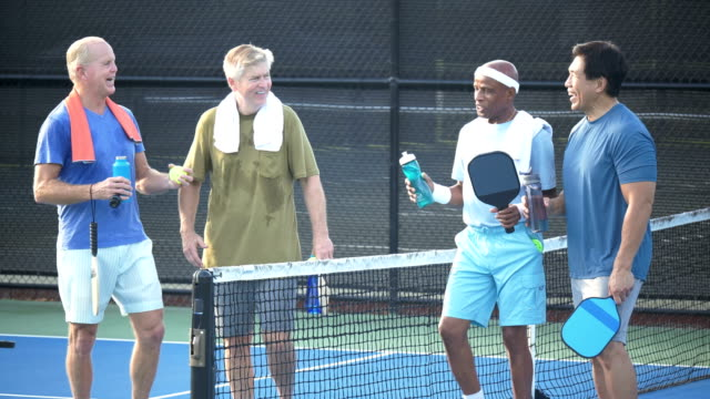 senior men walking off pickleball court after playing - small group of people stock videos & royalty-free footage