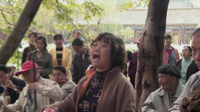 cu zo ms r/f senior men watching women dancing during festival, kunming, china - classical chinese garden stock videos & royalty-free footage