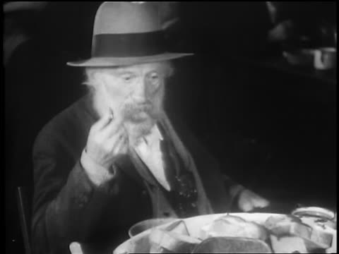 B/W 1929 senior men with beard eating in soup kitchen / Great Depression / newsreel