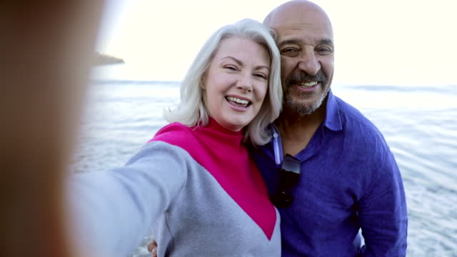 senior mixed couple taking a selfie at the beach - recreational pursuit stock videos & royalty-free footage