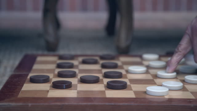 mcu senior mixed race  couple playing checkers by fireside/ cape town/ south africa - draughts stock videos & royalty-free footage