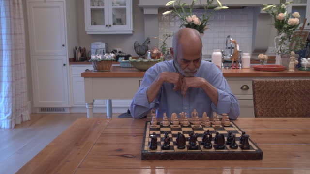 MS senior mixed race man playing chess in kitchen/ Cape Town/ South Africa