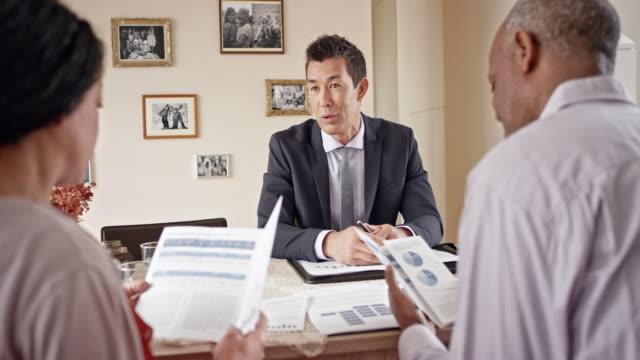Senior Multi ethnischen paar Beratung ein Asian Banker in ihrem Haus