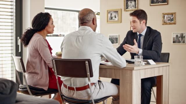 vídeos de stock, filmes e b-roll de sênior de multi étnica casal consultoria pessoal banqueiro em casa - consultor financeiro