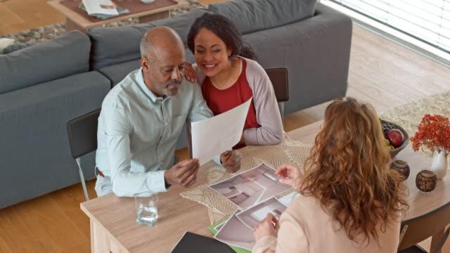 Senior multi ethnic couple discussing the design plans with their interior designer