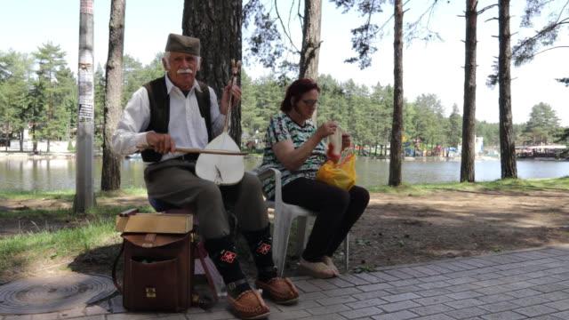 senior musiker in nationalkostüm spielen musikinstrument beim stricken frau - osteuropäische kultur stock-videos und b-roll-filmmaterial