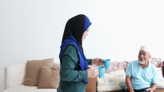 vídeos de stock, filmes e b-roll de casal de asiáticos muçulmanos sênior bebendo chá e assistindo televisão - vestuário modesto