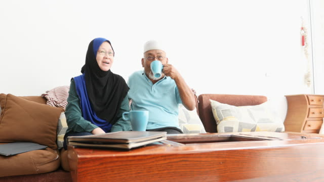 senior muslim asian couple drinking tea and watching television - malaysian ethnicity stock videos & royalty-free footage