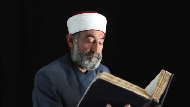 senior muslim imam in religious costume praying - holy book stock videos and b-roll footage