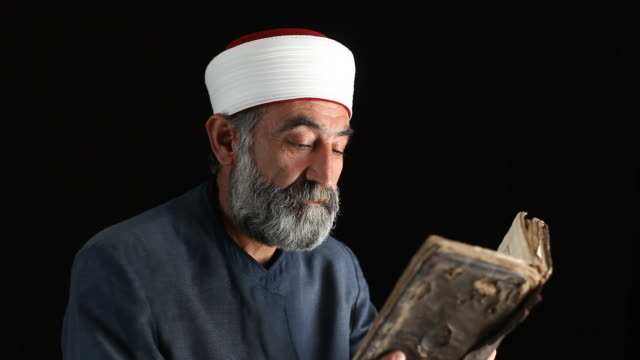 Senior muslim imam reading in dark
