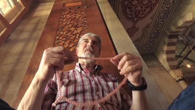 senior muslim man with prayer beads praying - islam stock videos & royalty-free footage