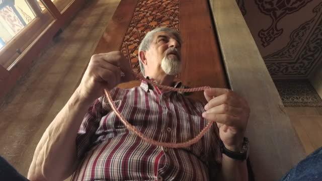 Senior muslim man with rosary praying