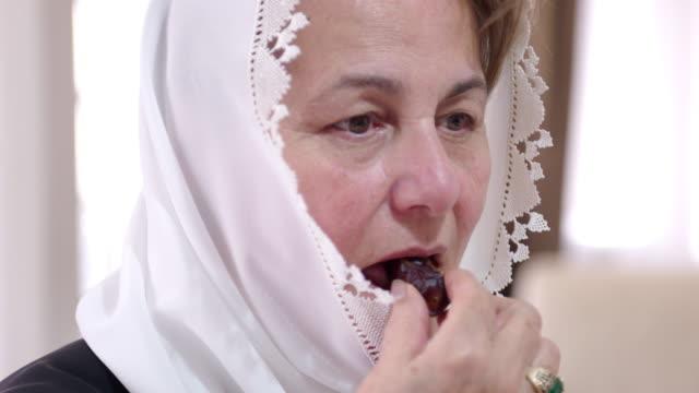 senior muslim woman eating dates - turks fruit stock videos and b-roll footage