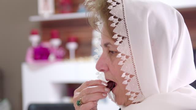senior muslim woman eating dates - ramadan stock videos & royalty-free footage