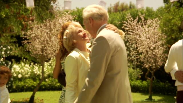 vídeos y material grabado en eventos de stock de cu, senior newly wed couple and wedding guests dancing in garden - eventos de la vida