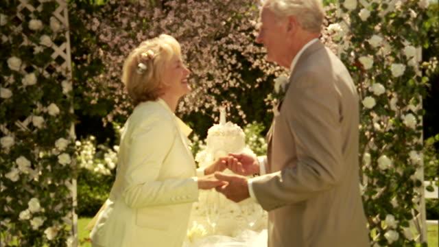 cu, zi, senior newly wed couple kissing in garden - jung geblieben stock-videos und b-roll-filmmaterial