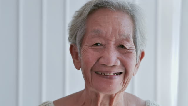 senior old gray-haired woman looking at camera in home.joyful nice elderly women smiling while being in a great mood.happy elder mature grandmother with toothy smile at home or retirement house - one senior woman only stock videos & royalty-free footage