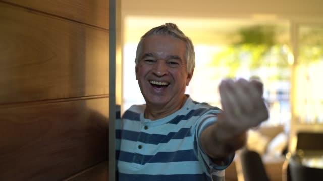 vídeos de stock, filmes e b-roll de senior, abrindo a porta da frente - gesticulando