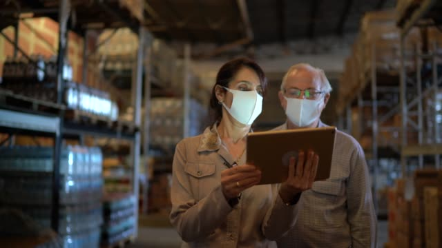 senior partners walking and using digital tablet at warehouse - with face mask - using digital tablet stock videos & royalty-free footage