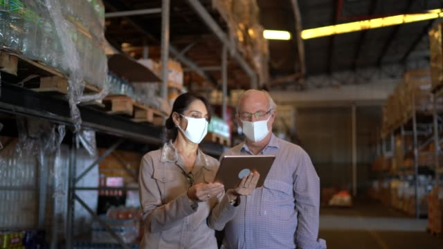 senior partners walking and using digital tablet at warehouse - with face mask - warehouse stock videos & royalty-free footage