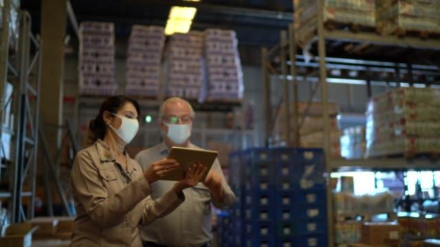 vídeos de stock e filmes b-roll de senior partners walking and using digital tablet at warehouse - with face mask - trabalhador de armazém