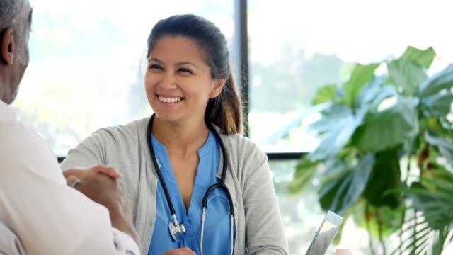 vídeos de stock, filmes e b-roll de médico de paciente e feminino sênior compartilhar um aperto de mão antes de sair - clínica médica