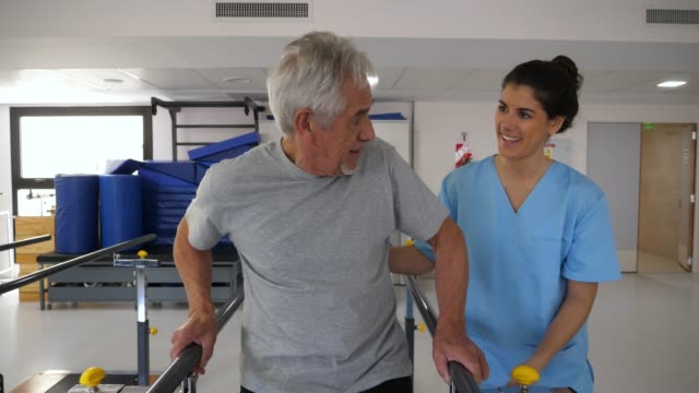 senior patient at physiotherapy walking slowly using the parallel bars with his therapist standing next to him correcting the movements - recovery stock videos and b-roll footage
