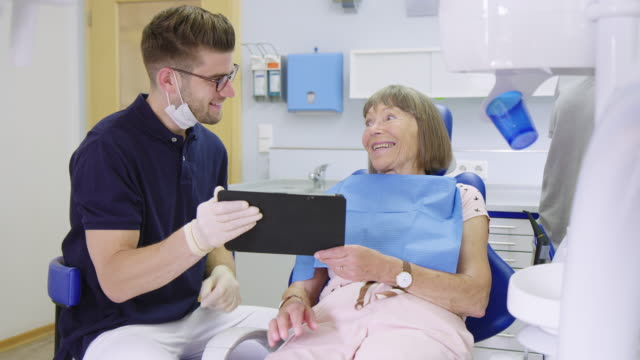 senior patient discussing with dentist over tablet - dental hygiene stock videos & royalty-free footage