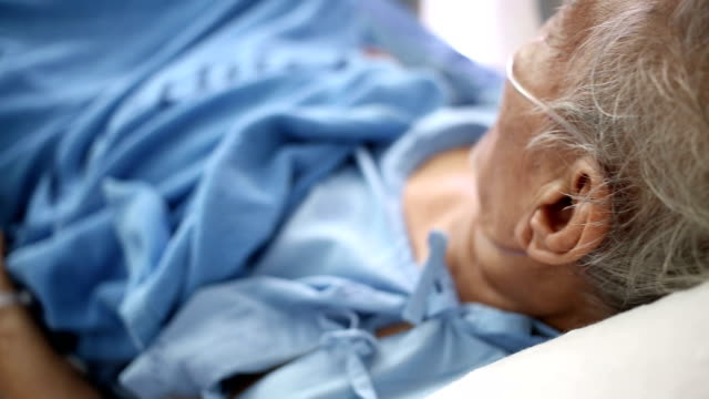Senior Patient in bed breathing oxygen mask