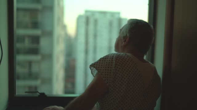 senior patient looking through window at hospital - mental health stock videos & royalty-free footage