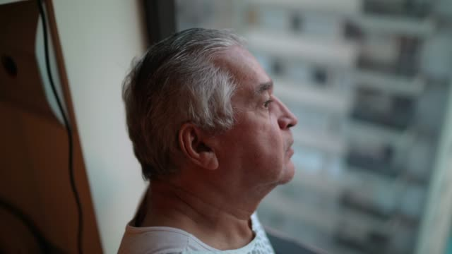 senior patient looking through window at hospital - patience stock videos & royalty-free footage